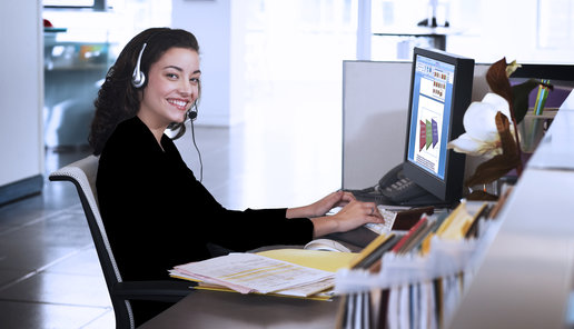 Businesswoman wearing headset at desk, smiling, portrait